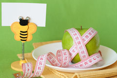 Green apple and measuring tape on a white plate Royalty Free Stock Photography