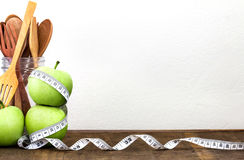 Green apple with Measuring tape on wooden background in concept Royalty Free Stock Photos