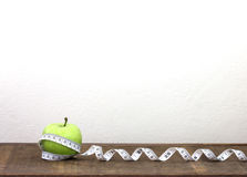 Green apple with Measuring tape on wooden background in concept Royalty Free Stock Photography
