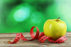 Green apple with measuring tape on wooden background Stock Photos