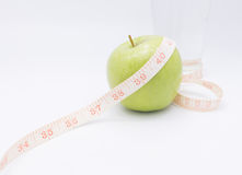 A green apple with a measuring tape wrapped around it for the co royalty free stock photography