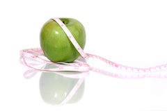 Green apple and measurment tape. Over white Stock Image