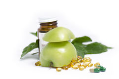 GREEN APPLE WITH MEDICINE BOTTLE. Sliced green apple with medicine bottle and capsules on white background Royalty Free Stock Photography