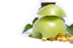GREEN APPLE WITH MEDICINE BOTTLE 2. Sliced green apple with medicine bottle and capsules on white background royalty free stock images