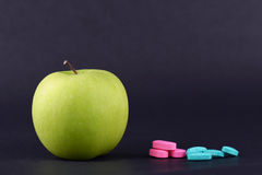 GREEN APPLE AND MEDICINE 2. One whole green apple and medicine on black background stock images