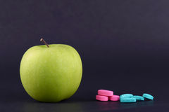 GREEN APPLE AND MEDICINE. One whole green apple and medicine on black background Stock Photo