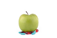 GREEN APPLE WITH MEDICINE. Whole green apple with capsules, tablets and pills on white background stock image