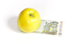 Green apple and money. Green apple lying on the banknote, on a white background royalty free stock photo