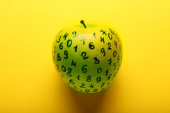Green apple with numbers on yellow background Royalty Free Stock Image