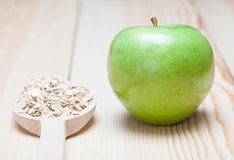 Green apple and oat-flakes in the wooden spoon Royalty Free Stock Photos