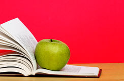 Green apple and open book Stock Image