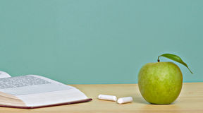 Green apple and open book. Green apple,  pieces of chalk, and open book on desk Stock Photo