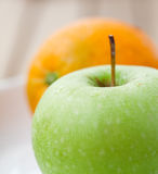 Green apple with an orange in the back Royalty Free Stock Images