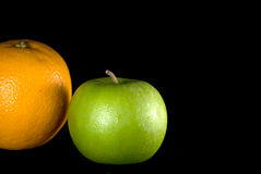 Green apple and orange fruit. Green apple and an orange isolated on a black background Royalty Free Stock Photo