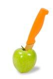 Green apple and orange knife Stock Photos