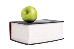 Green apple over a open book Stock Photos