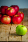 Green apple over red apples. Isolated green apple among red apples royalty free stock photos