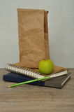 A green apple. a paper lunch bag and a stack of books Royalty Free Stock Photography