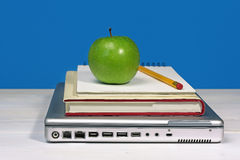 Green apple, pencil and book on laptop Stock Images