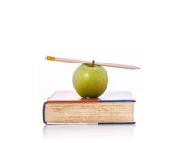 Green apple and pencil on book. Studio shot isolated on white Stock Photography