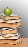 Green apple on pile of books Stock Photos