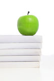 Green apple on pile of books Stock Photo