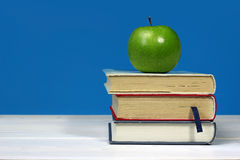 Green apple on pile of books Stock Images