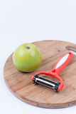 Green apple and plastic peeler on the kitchen board Royalty Free Stock Photography