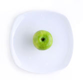 Green apple in the plate. Green Apple in the white plate on the white background Royalty Free Stock Photo