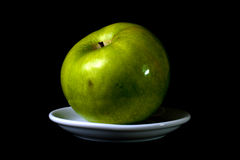 Green apple on a plate Royalty Free Stock Image