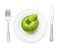 Green apple on plate with fork and knife Stock Photos