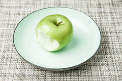 Green apple on plate, missing bite Royalty Free Stock Images