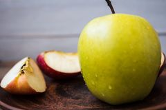 Green apple on a plate on wooden background royalty free stock images