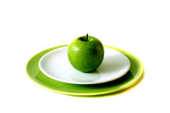 Green apple on plates. A single green apple is placed on top of two plates, isolated on a white background royalty free stock images