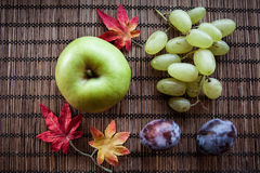 Green Apple and plum autumn leaves on wooden background. Autumn leaves and green Apple  on wooden background plum Royalty Free Stock Image