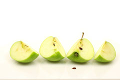 Green apple quarters. On a white background Stock Photos