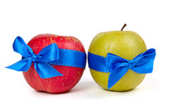 Green apple and red apple with blue ribbons Stock Photography