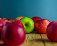 Green apple among red apple. Isolation of apple among red apples royalty free stock photo