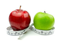 Green Apple and Red Apple with measuring tape. On white background royalty free stock photo