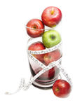 Green apple and  red apple with measuring tape in glass bowl Stock Images