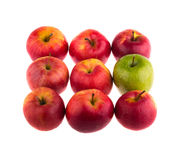 Green apple among red apples Stock Photos