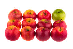 Green apple among red apples Stock Photo