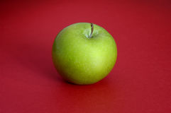 Green apple on red background. Closeup stock photography
