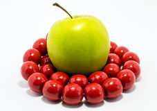 Green apple with red  beads. Green apple with red large beads Royalty Free Stock Photos