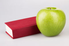 Green apple with red book on white Royalty Free Stock Photos