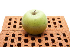 Green apple on red brick stone Stock Image
