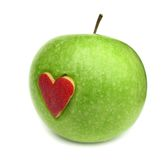 Green apple with red heart on it Royalty Free Stock Image