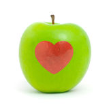 Green apple with red heart Stock Image