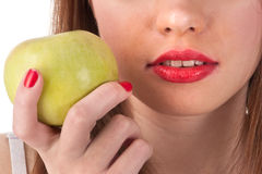The green apple and red lips. The beautiful girl's lips and green apple in her hand Stock Images