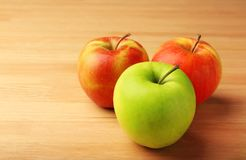 Green apple among red ones. On wooden background. Difference and uniqueness concept stock image
